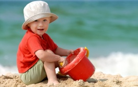 Baby Boy Playing On Beach Sand
