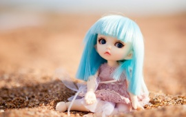 Blue Hair Doll Sitting At Sand