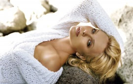Charlize Theron lying on a rock