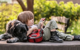 Cute Boy Playing Guitar With Dog
