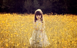 Cute Child In A Flower Field